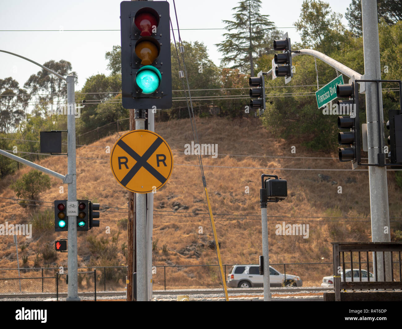 Railroad crossing sign on a track intersection on a busy street with hill - Stock Image