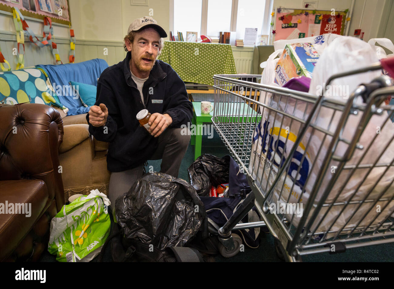 Tony Lee, a needy family man, is looked after by volunteer helpers at the Arnold Food Bank Daybrook Baptist Church's food store in Nottingham and provided with donated food for his family. Stock Photo