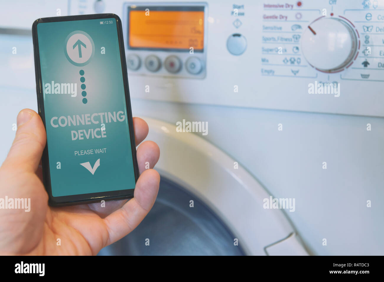 Connecting Washing machine with smart phone. Smart home and Internet of Things IoT concept - Stock Image