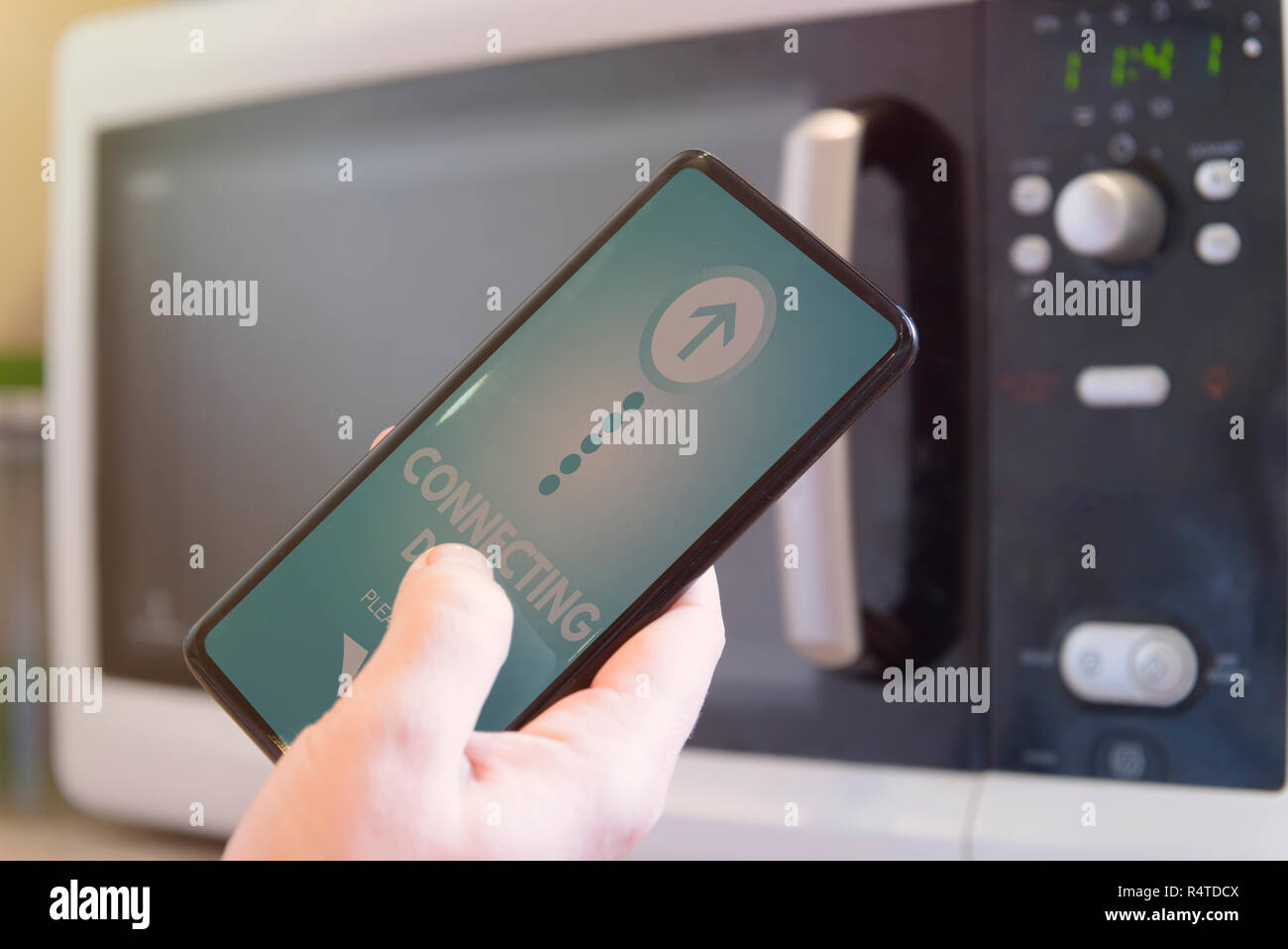 Connecting microwave oven with smart phone. Smart home and Internet of Things IoT concept - Stock Image