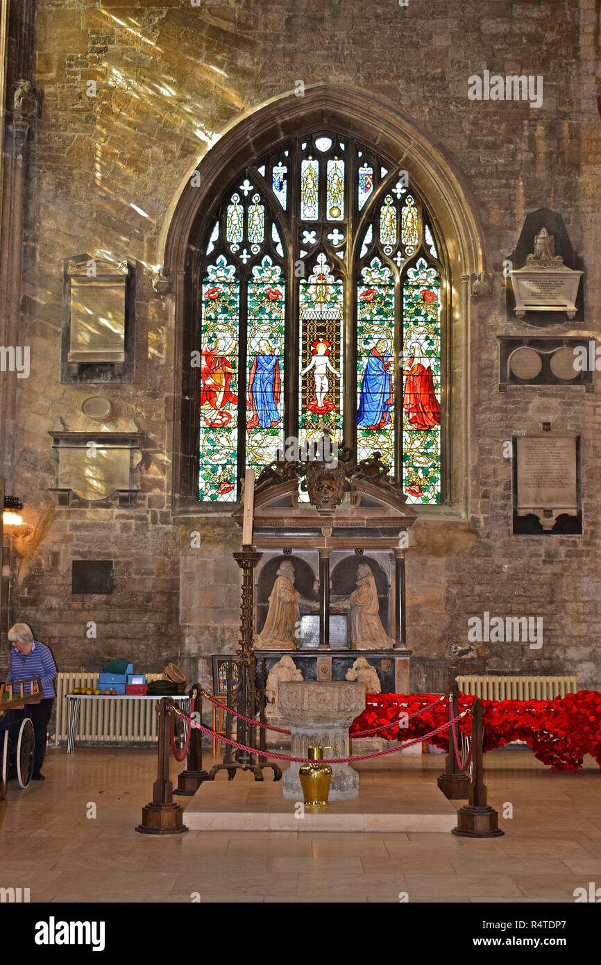 An ornate stained glass window within the Church of St John the Baptist in the market square of Cirencester with a stone font in the foreground. - Stock Image