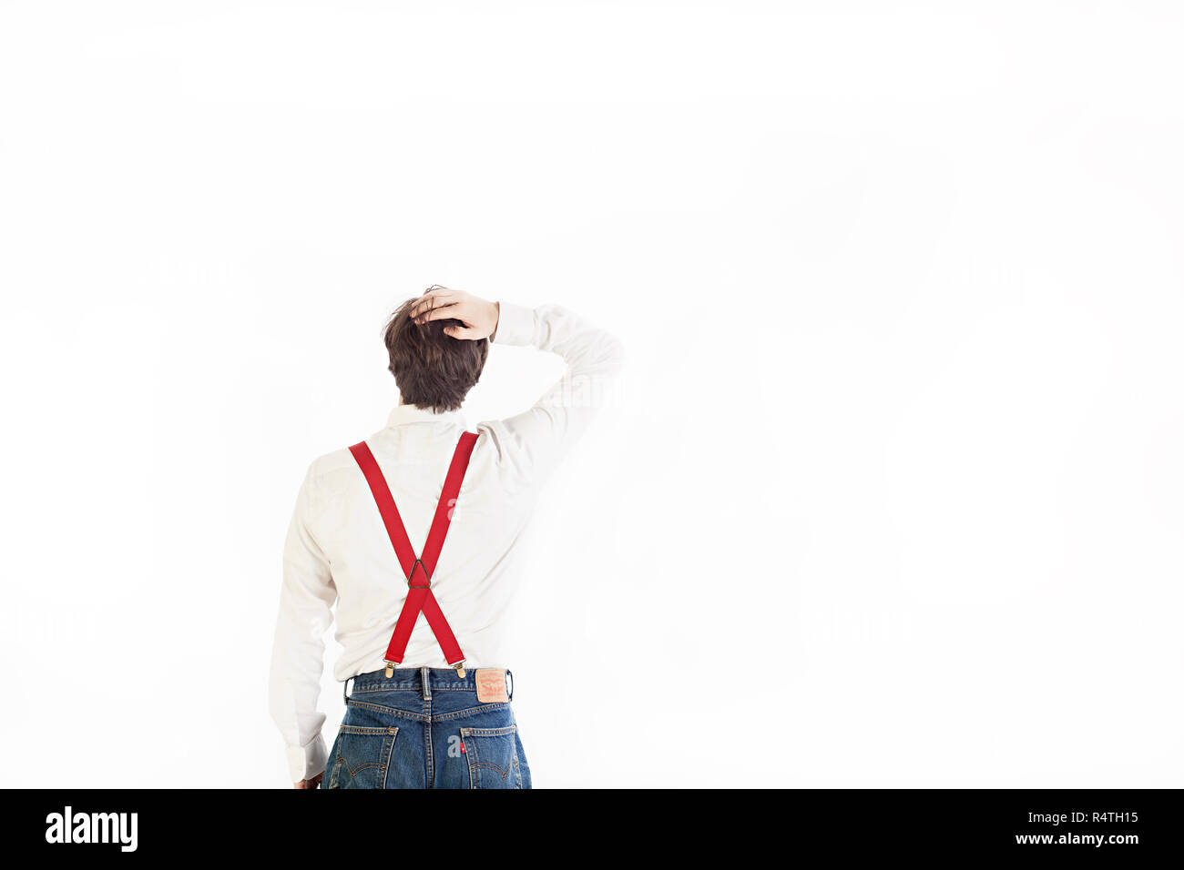 A man in a white shirt and red suspenders has his back to the camera and is looking up Stock Photo