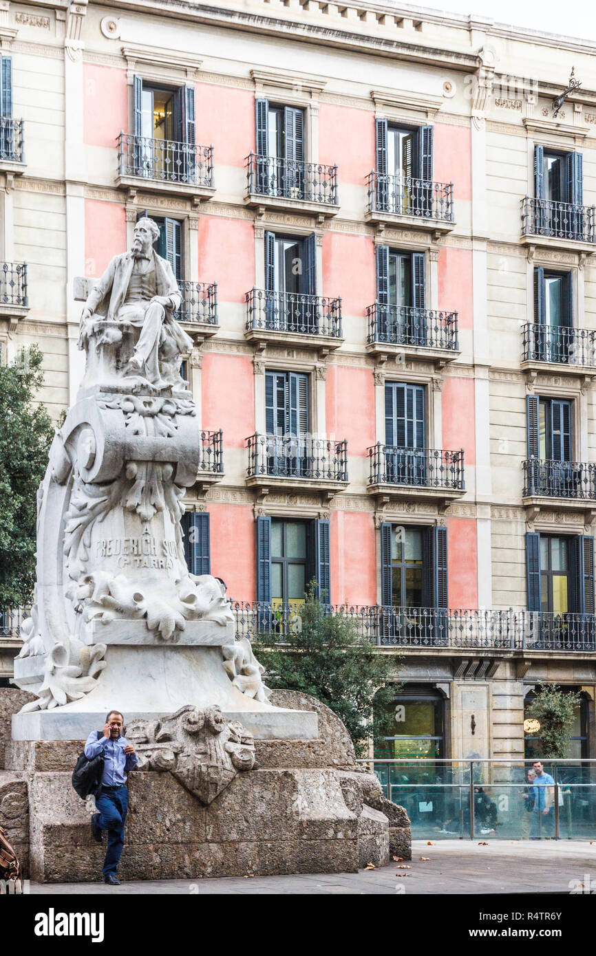 Barcelona, Spain - 4th October 2017: Man  on mobile phone leaning against a statue of Frederich Soler in the Placa del Teatre. Best known as 'Serafí P - Stock Image