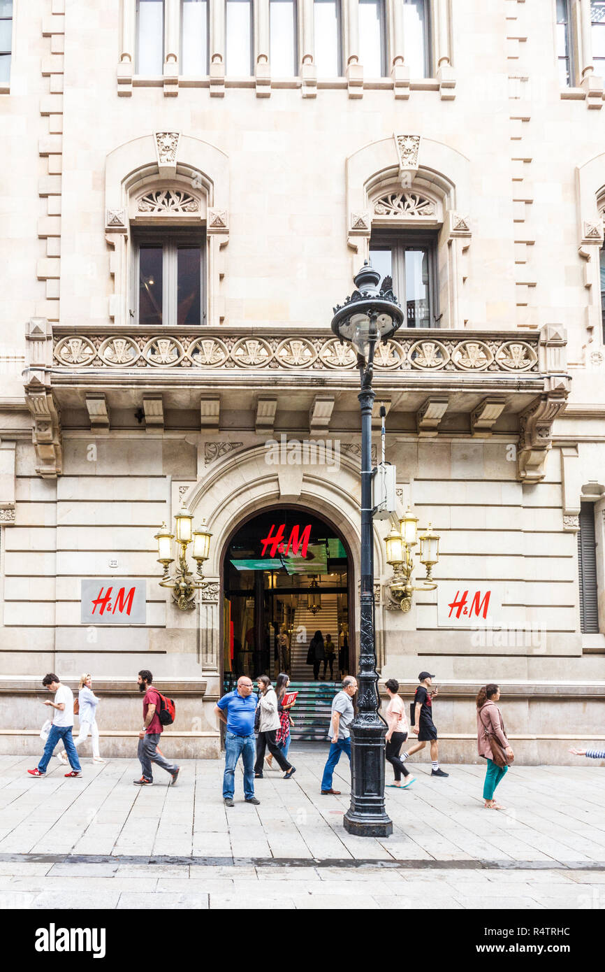 Barcelona, Spain - 4th October 2017: People walking past the H & M clothing store. Hennes & Mauritz AB is a Swedish multinational clothing-retail comp - Stock Image