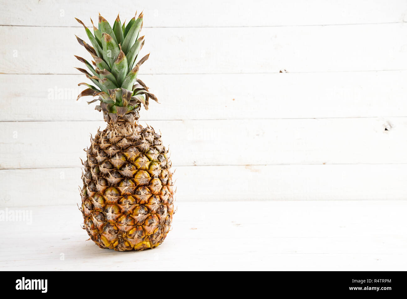 organic pineapple fruit on white painted wood, generous copy space - Stock Image