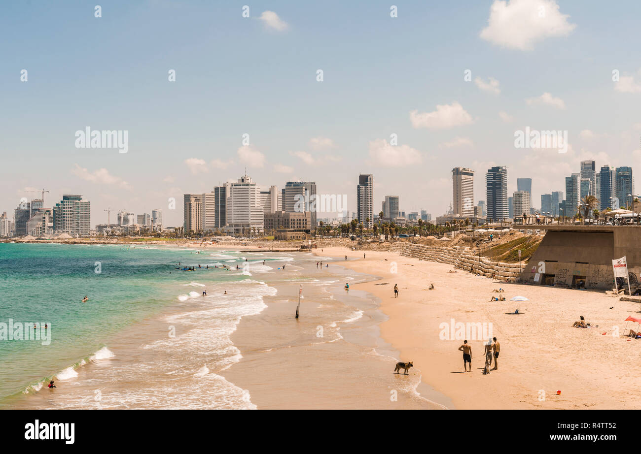 People on the beach, Alma Beach, view of skyline of Tel Aviv with skyscrapers, Tel Aviv, Israel - Stock Image