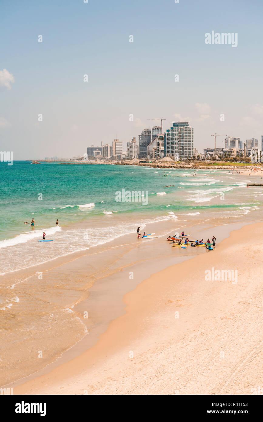 People on the beach, Alma Beach, view of skyline of Tel Aviv with skyscrapers, Tel Aviv, Israel - Stock Image