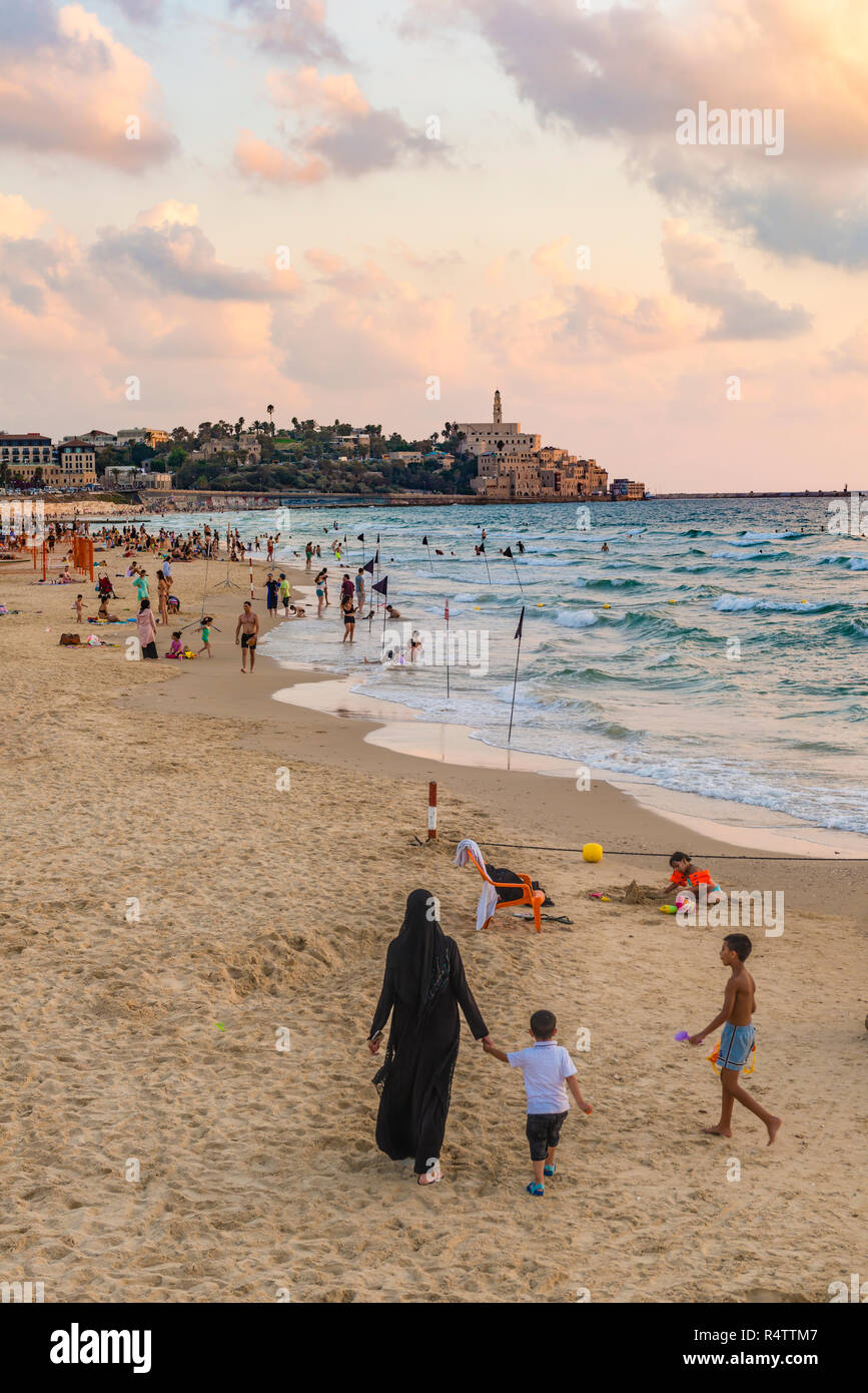 Locals on the beach, woman with burka and small child, evening mood, Alma Beach, behind Tel-Aviv-Jaffa, Old Town, Tel Aviv - Stock Image