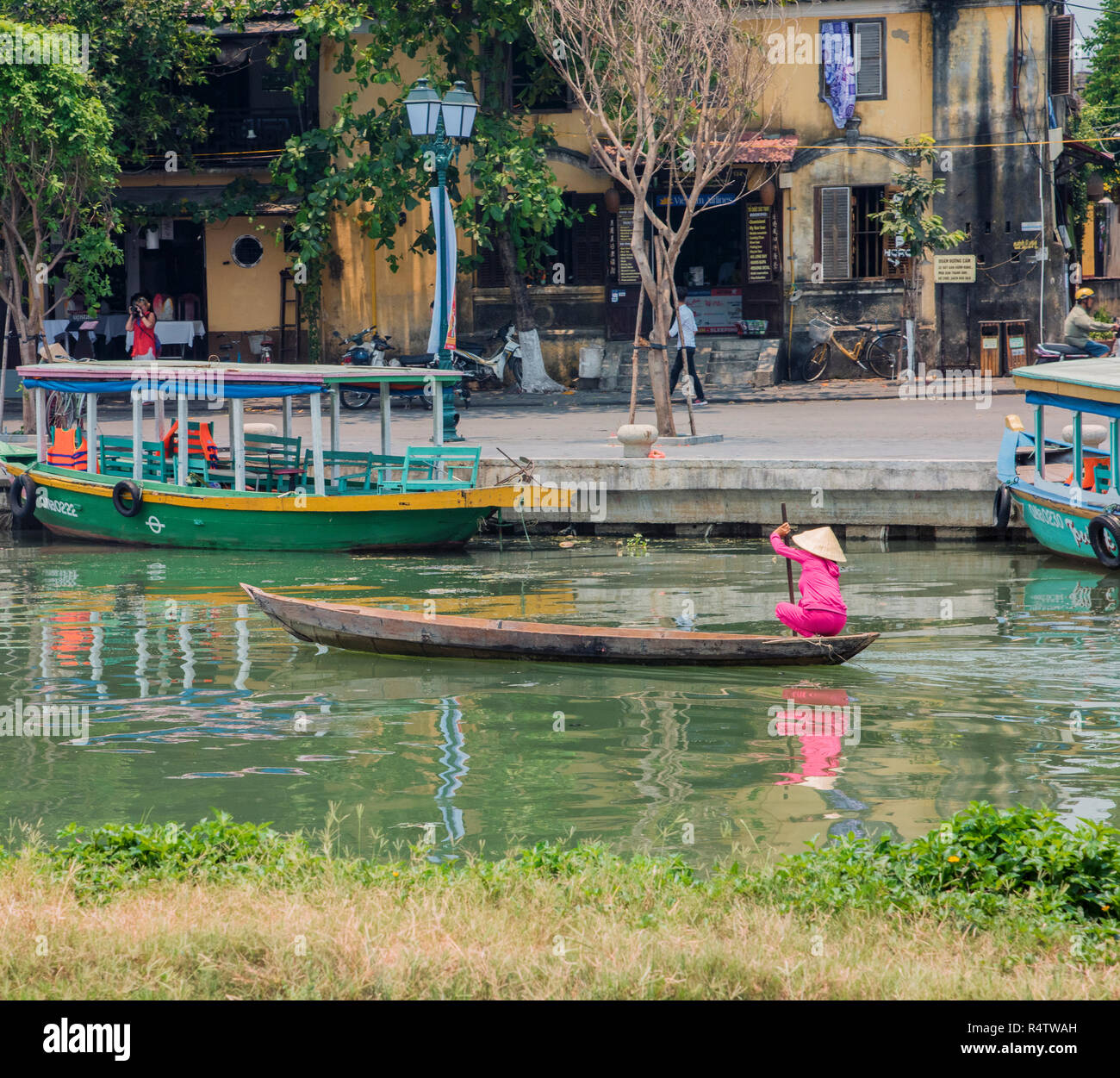 Hoi An a traditional Vietnamese lady rowing a boat across the river Bon in Hoi An Town Vietnam. - Stock Image