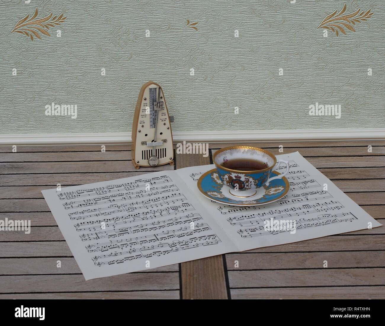 English teacup with saucer, fine bone china porcelain, and a metronome for music on a sheet of music - Stock Image