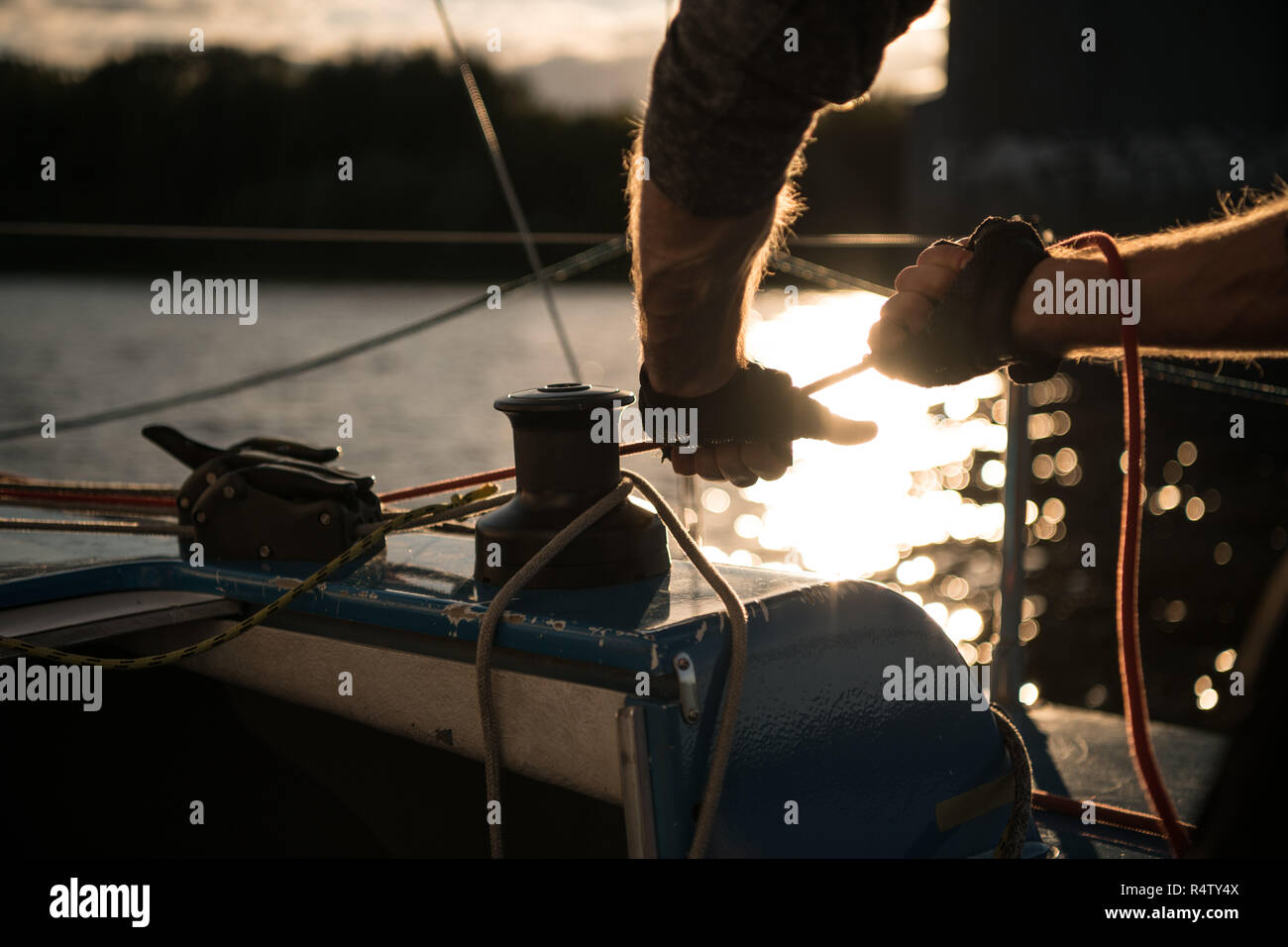 Silhouette of a sailors hands on a winch rope on a sailboat on a sunset. Shot with a selective focus. - Stock Image
