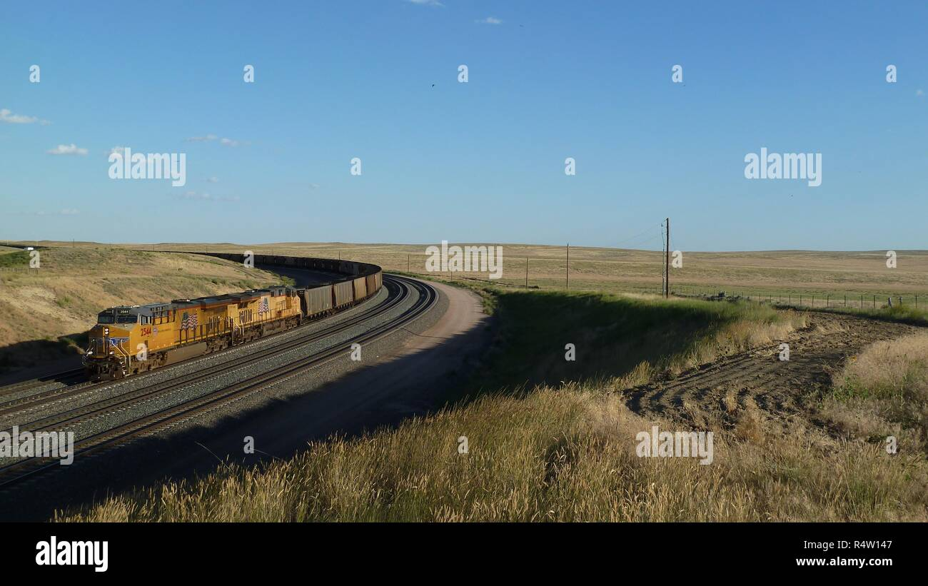 Locomotive and long coal train transporting coal in the Powder River Basin of Wyoming / USA. Stock Photo