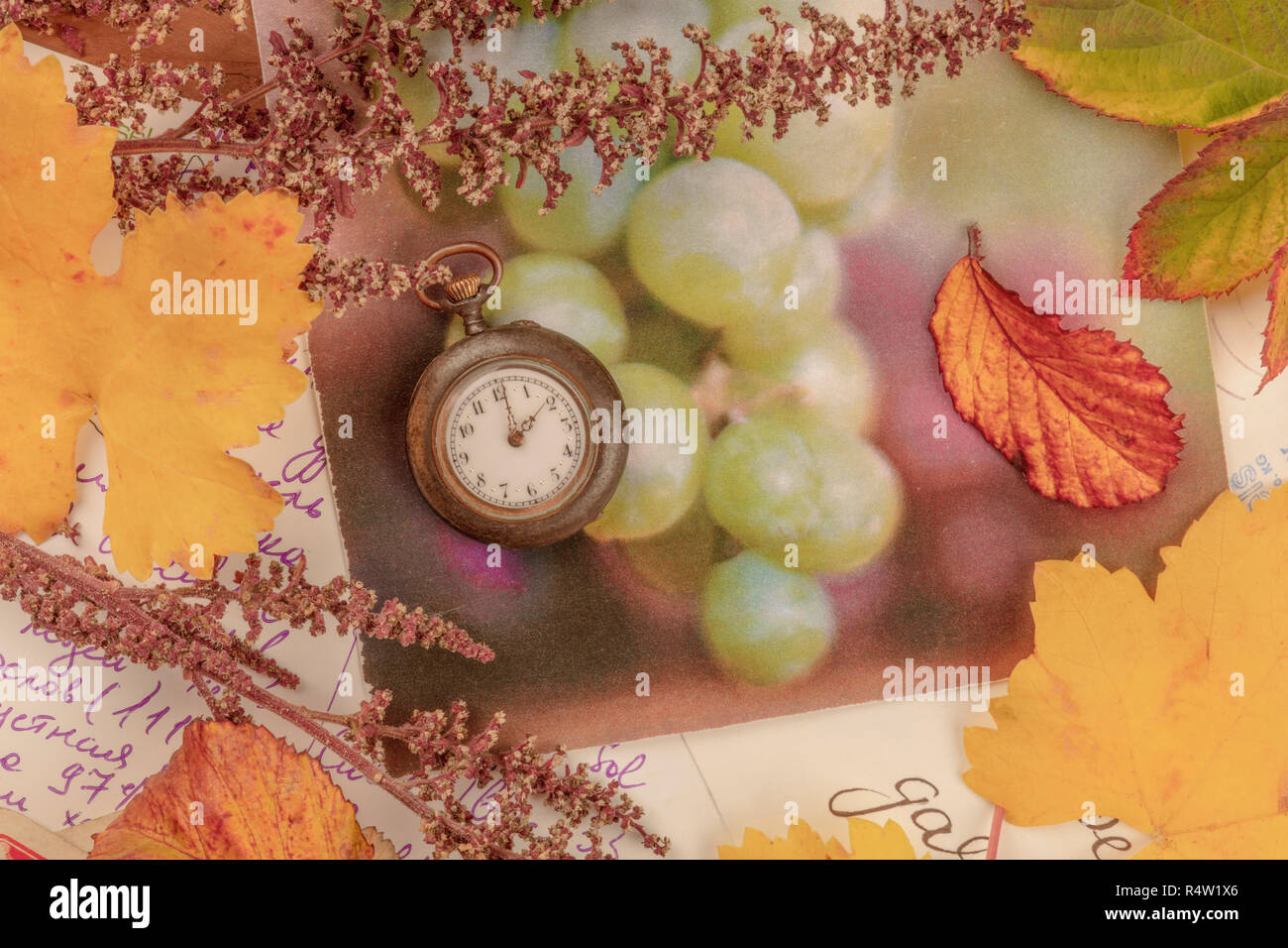 Nostalgia. A vintage pocket watch with autumn leaves and old postcards, shot from the top, toned image - Stock Image
