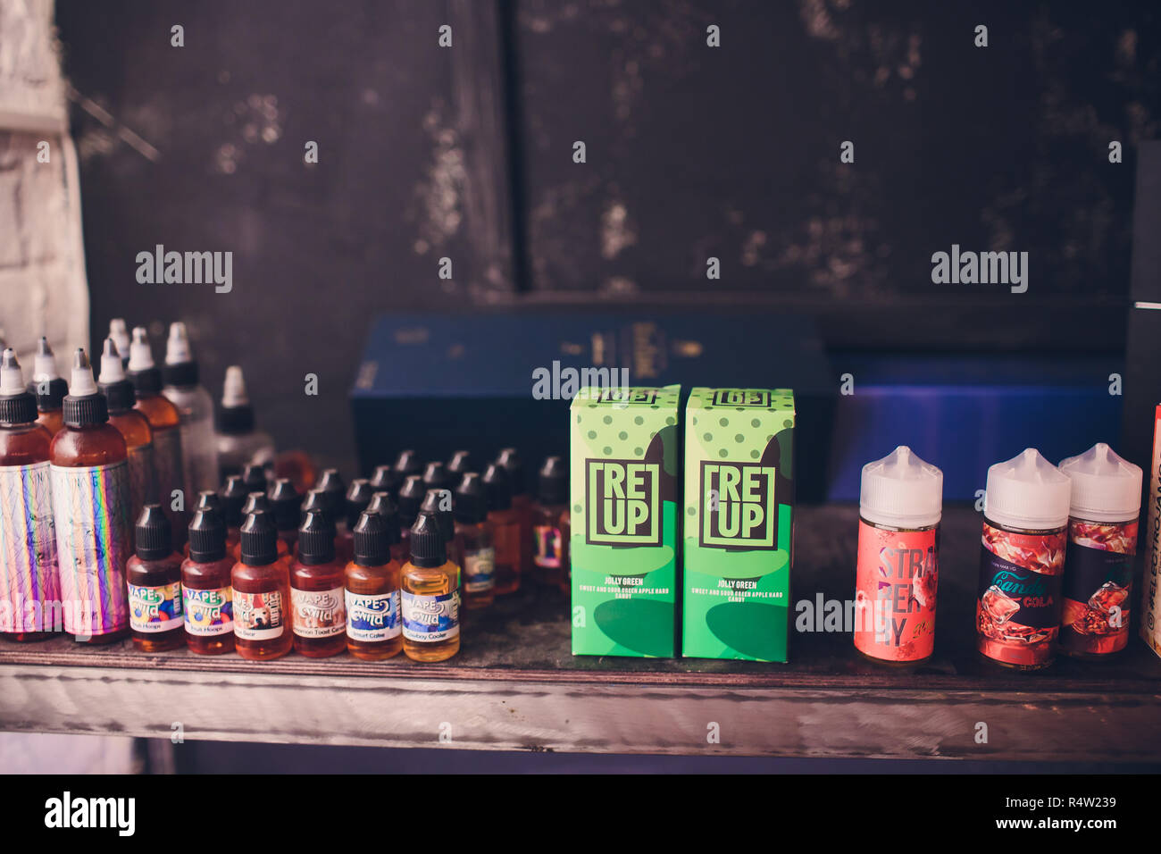 Ufa, Russia, South Vape Shop, 5 November, 2018: E-liquid e-juice High vape for electronic cigarette vaping device , on counter in smoke vapor in vape bar in bottles. - Stock Image