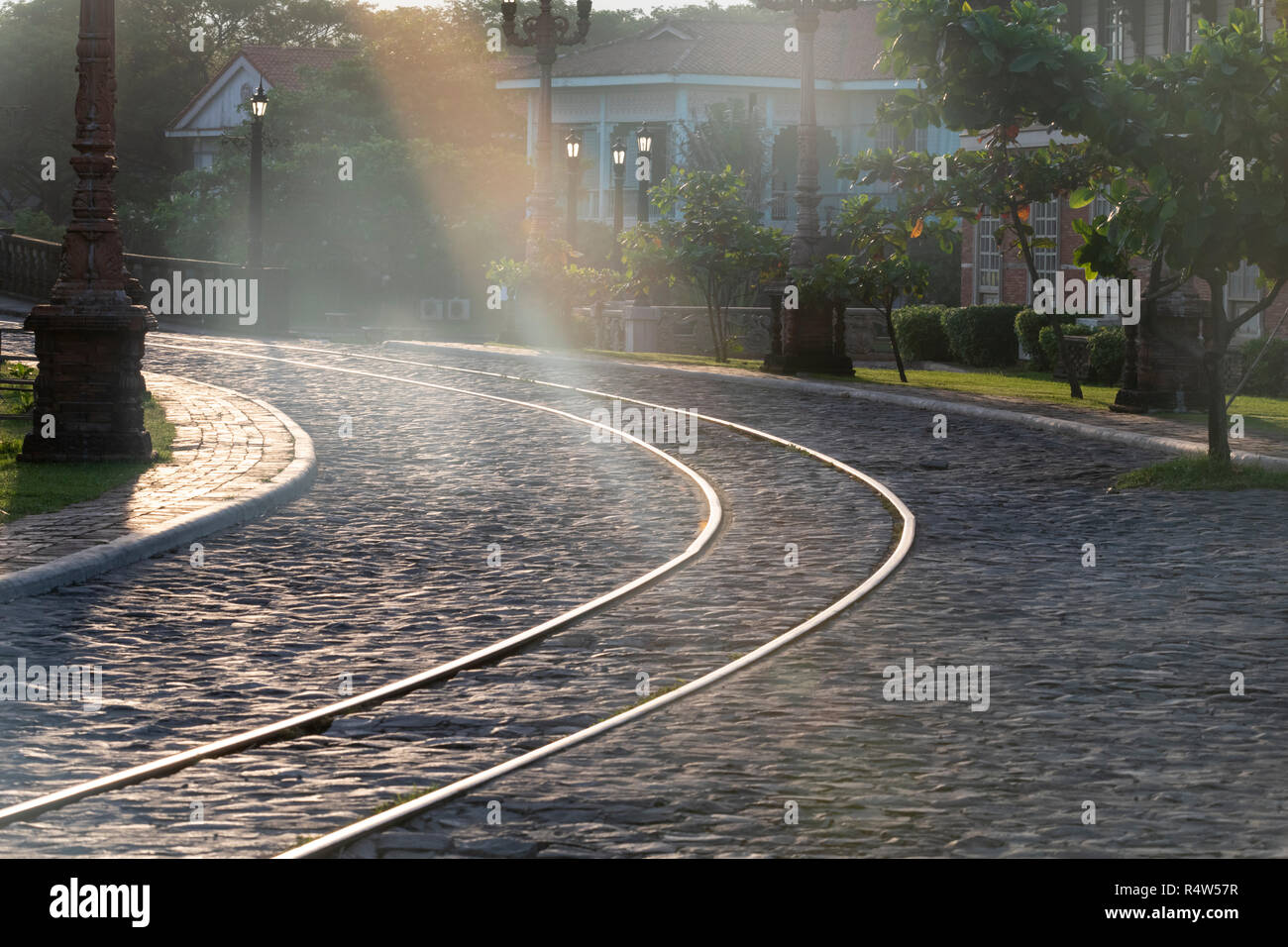 Shards of sunlight and the olde-worlde historic cobbled street with tram tracks lines day - Stock Image