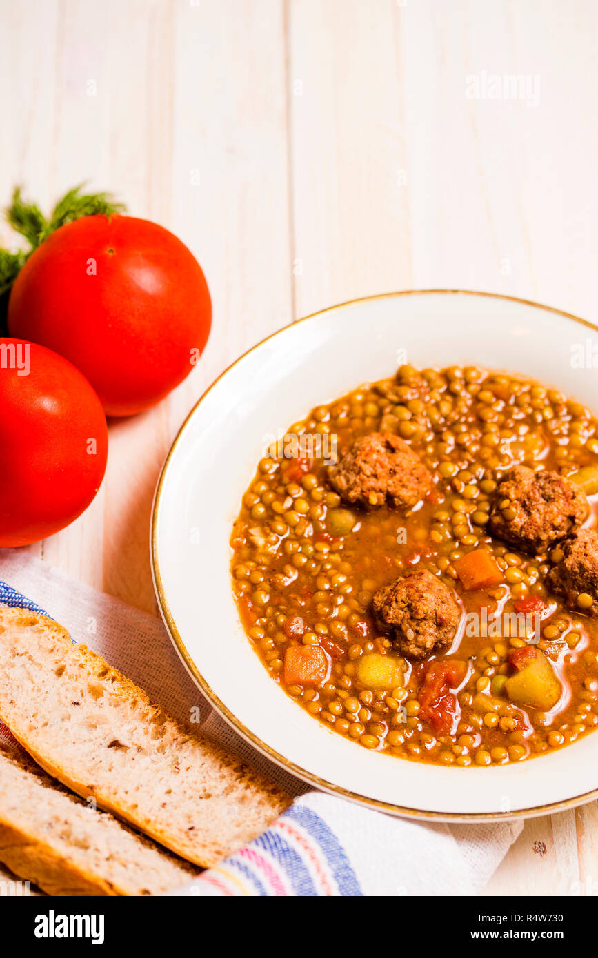 Lentil soup with fricandel, tomatoes and bread. Copy space - Stock Image