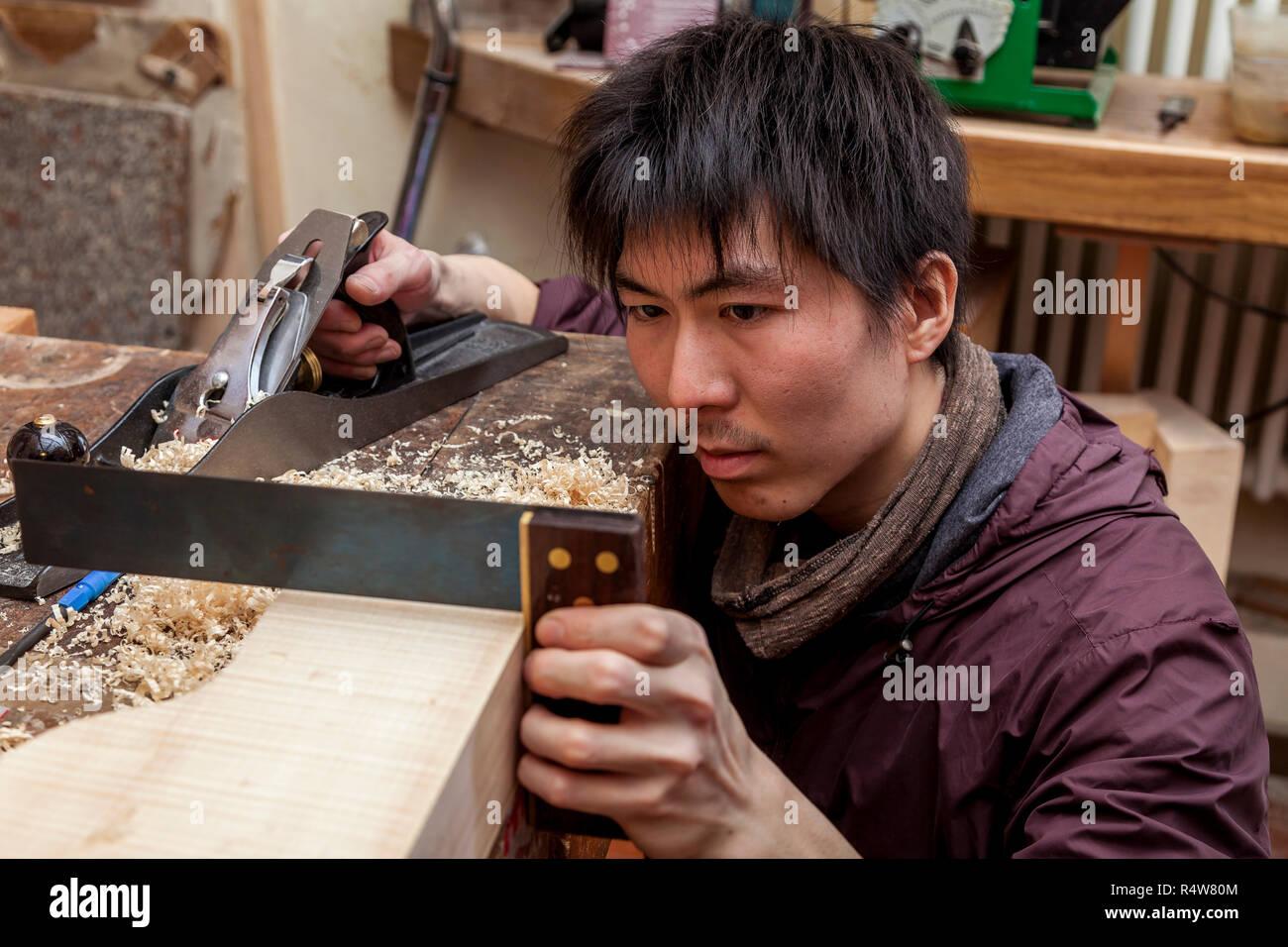 craftsman japaneese violinmaker began working on a new violin in his workshop - Stock Image