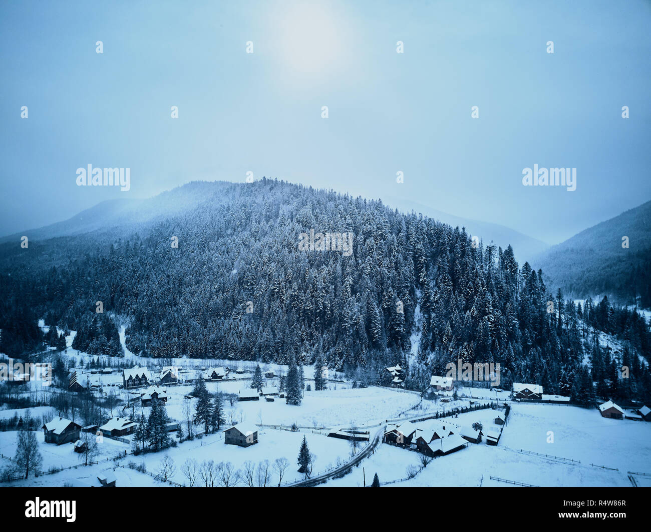 Aerial view of foggy countryside and houses in snowy valley. Hills and mountains with pine tree forest covered in snow. Multi-layered mountain landscape. Ski resort and traveltheme. Moody weather. - Stock Image