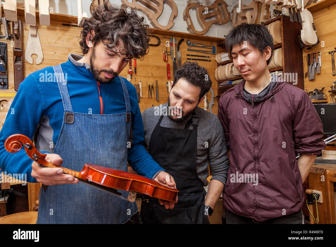 group of craftsmen violinmakers testing a new violin in their laboratory - Stock Image