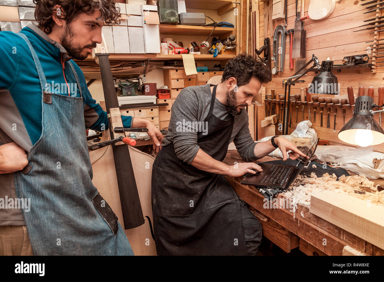 two craftsmen violinmakers checking data and measures for a new violin with computer - Stock Image