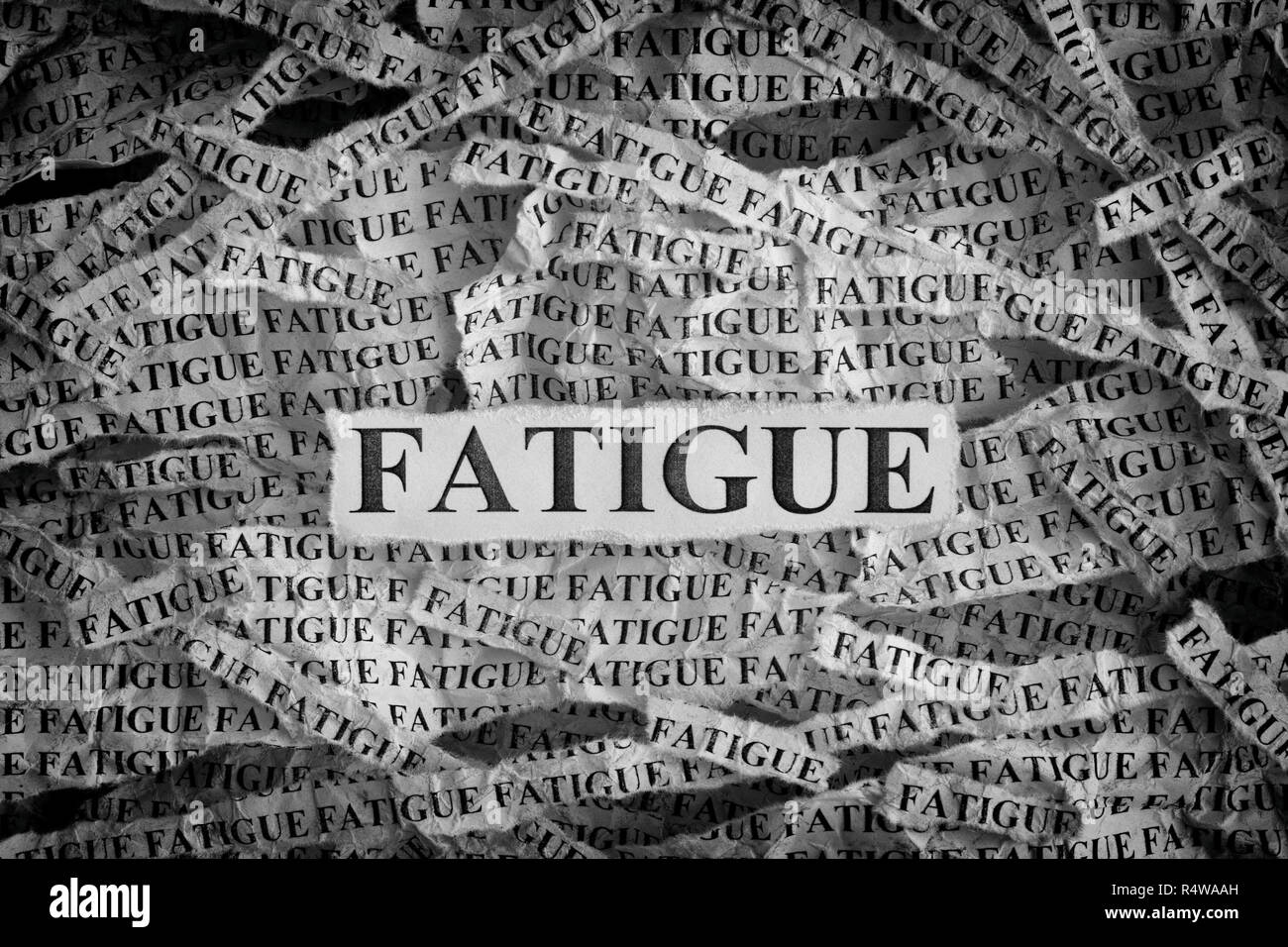 Fatigue. Torn pieces of paper with the word Fatigue. Concept Image. Black and White. Closeup. - Stock Image