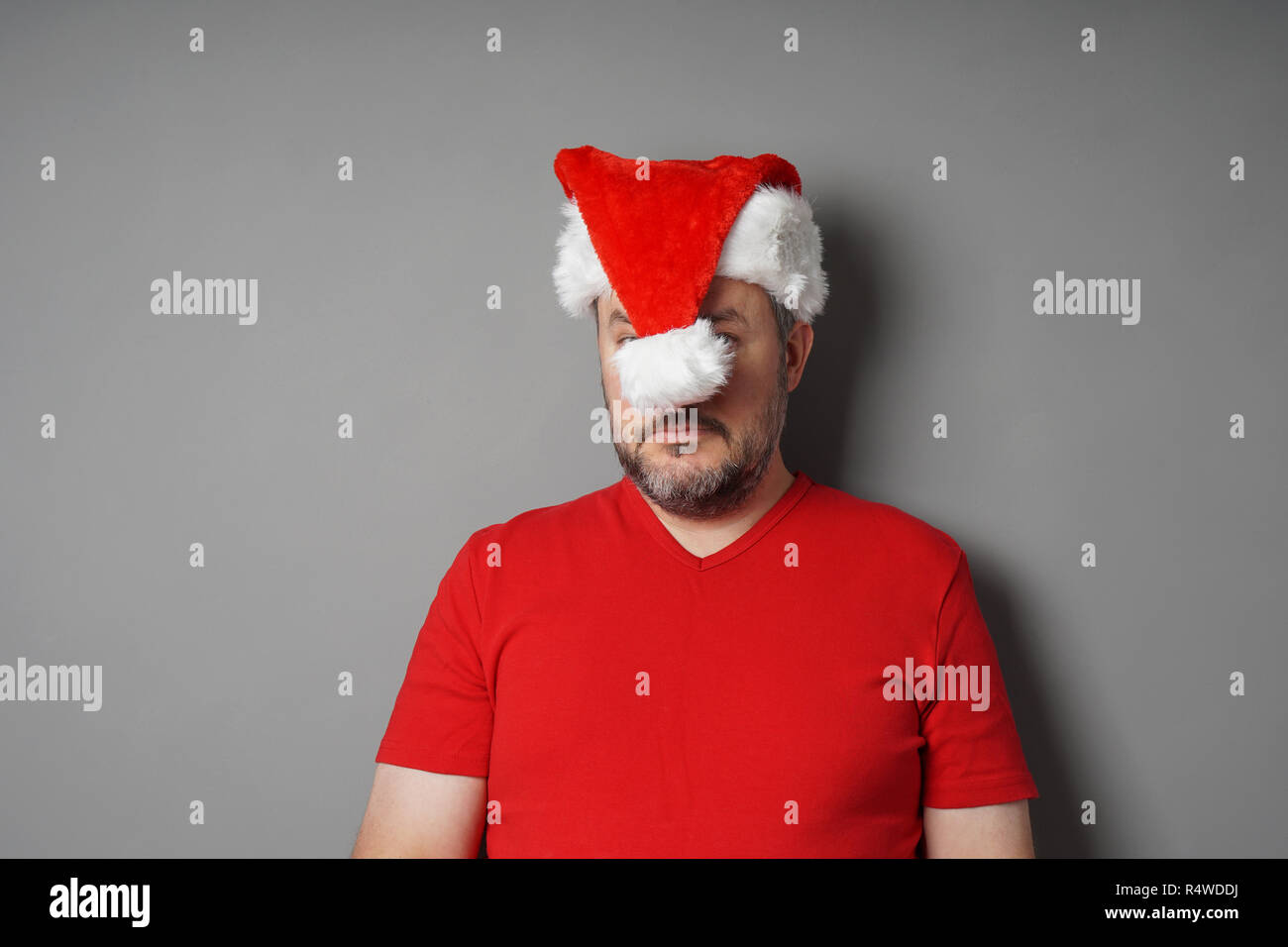 man hiding his face behind santa claus hat - christmas hater or holiday depression concept - Stock Image