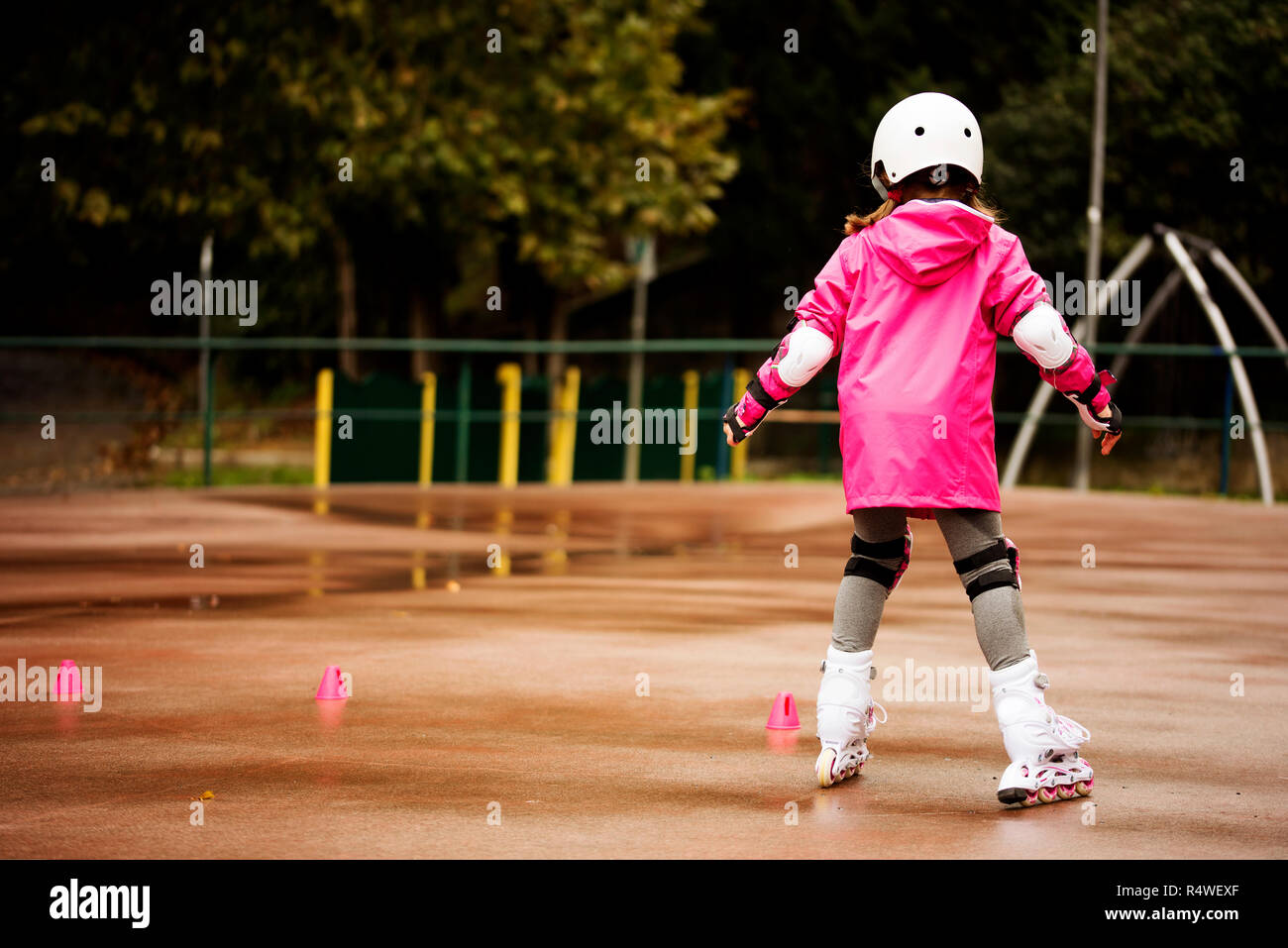A little caucasian girl beginner roller in the autumn park in the rainy day. - Stock Image