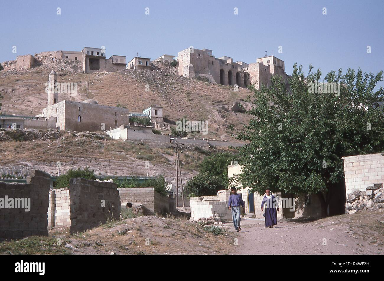 View of local residents walking a dirt road in the inhabited town of Qalaat Al-Madiq, adjacent to the ancient ruins of Apamea, Syria, June, 1994. () - Stock Image