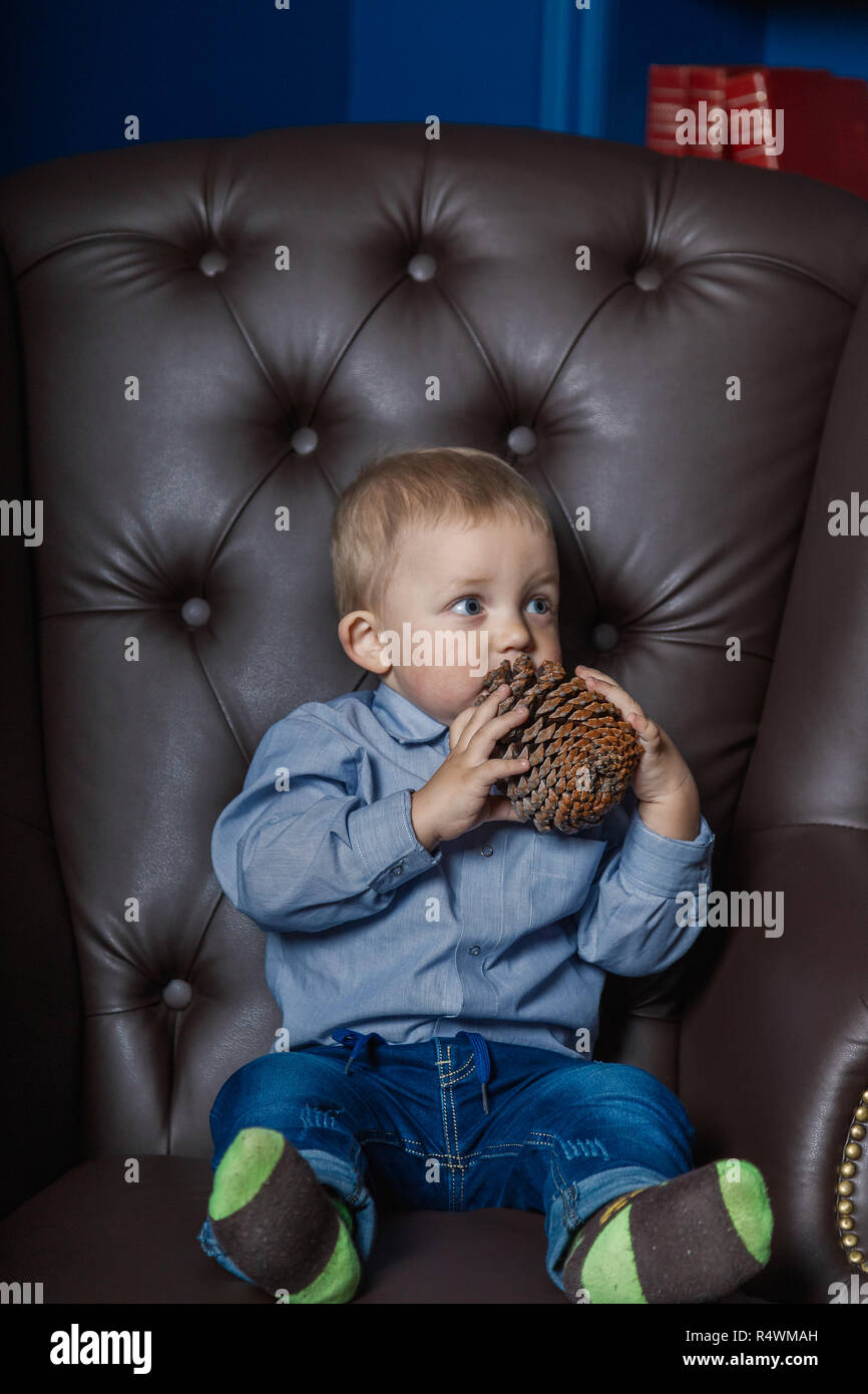 A little boy is sitting in an old leather chair - Stock Image