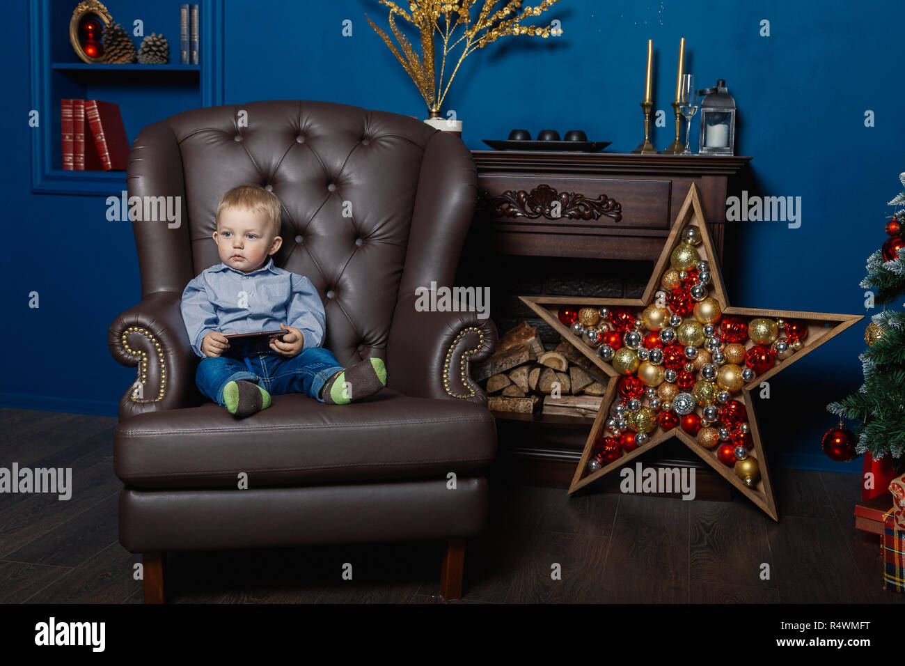 A little boy is sitting in an old leather chair with a phone - Stock Image