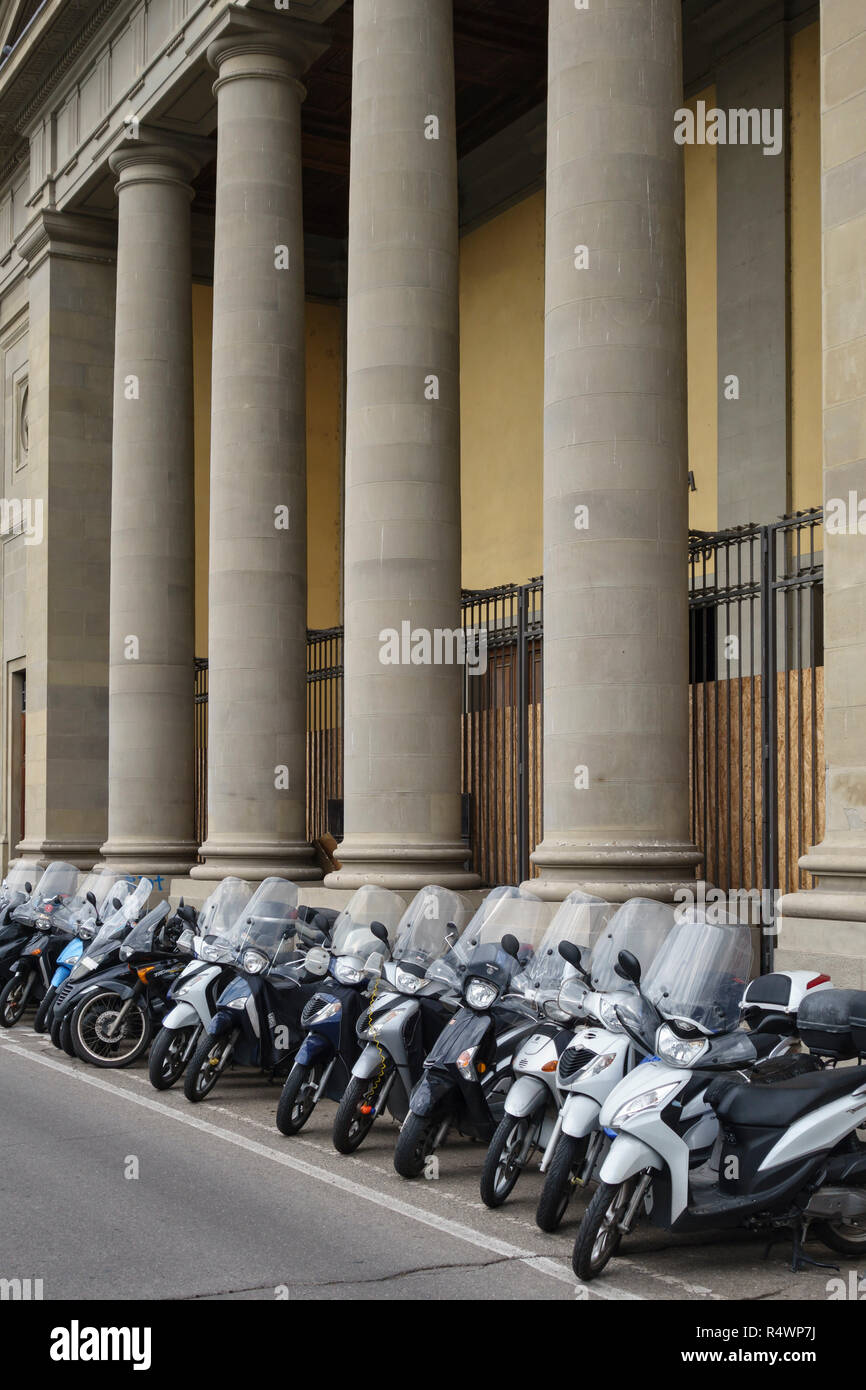 Florence, Tuscany, Italy. A long row of neatly parked motorcycles, mopeds and scooters - Stock Image