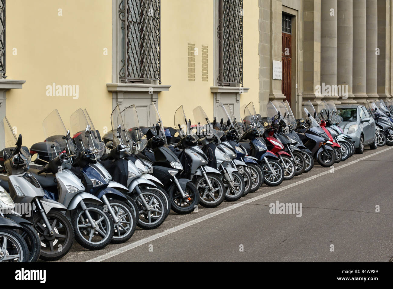 Florence, Tuscany, Italy. A long row of neatly parked motorcycles, mopeds and scooters, with a small car squeezed in - Stock Image