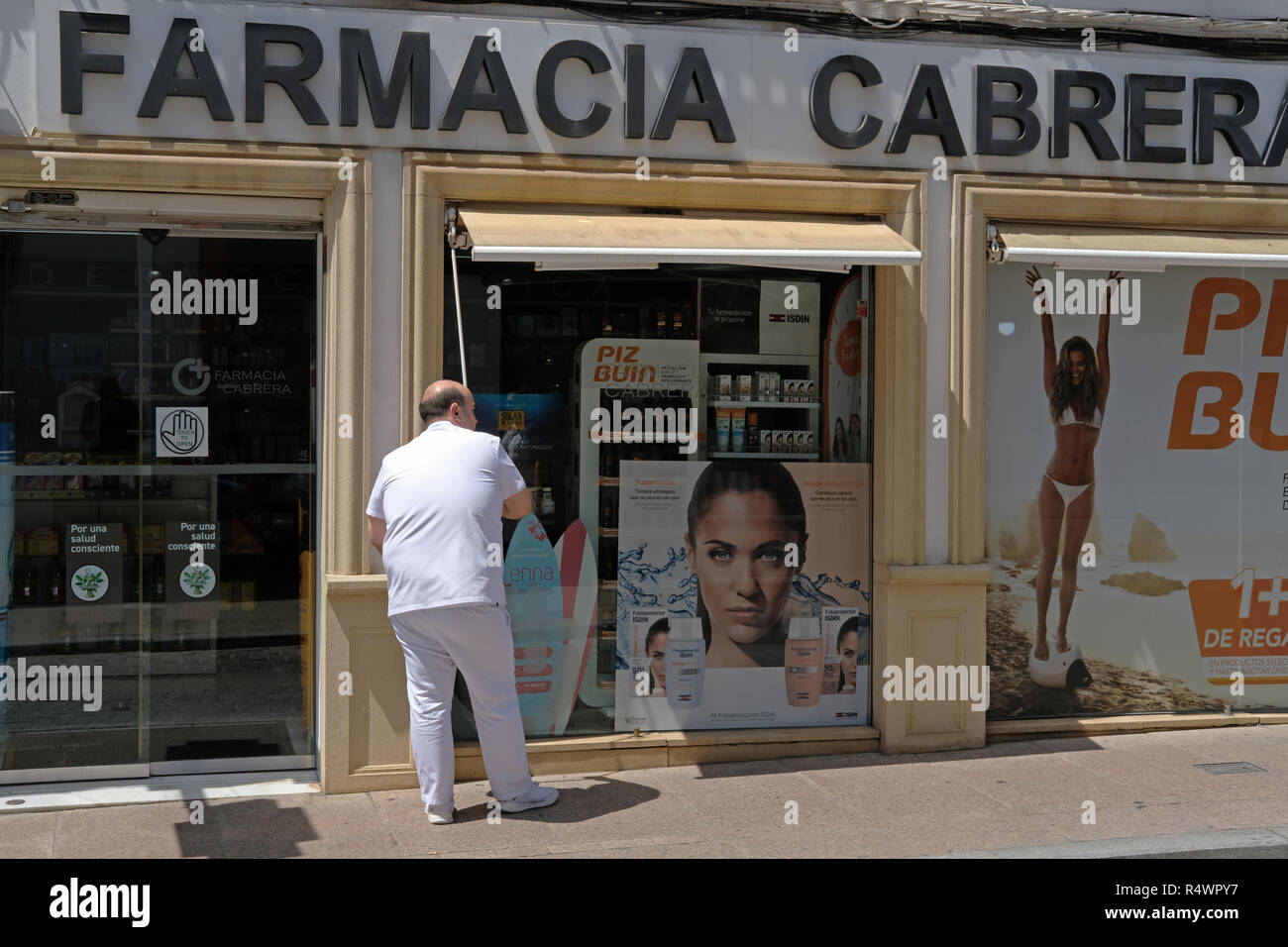 A man closing a pharmacy in Andulacia, Spain for the siesta. - Stock Image
