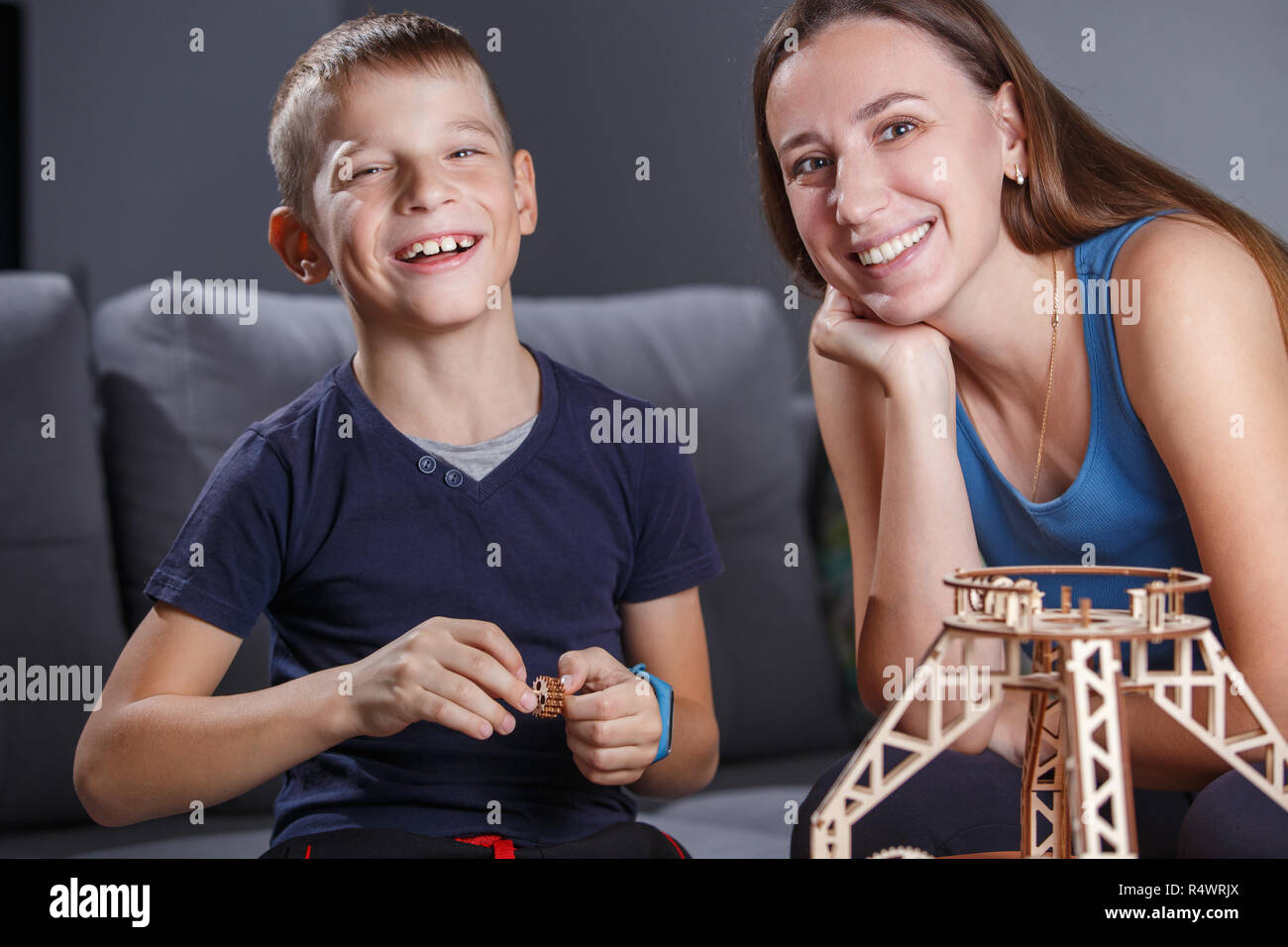 Young boy assembling wooden constructor with his mother. - Stock Image
