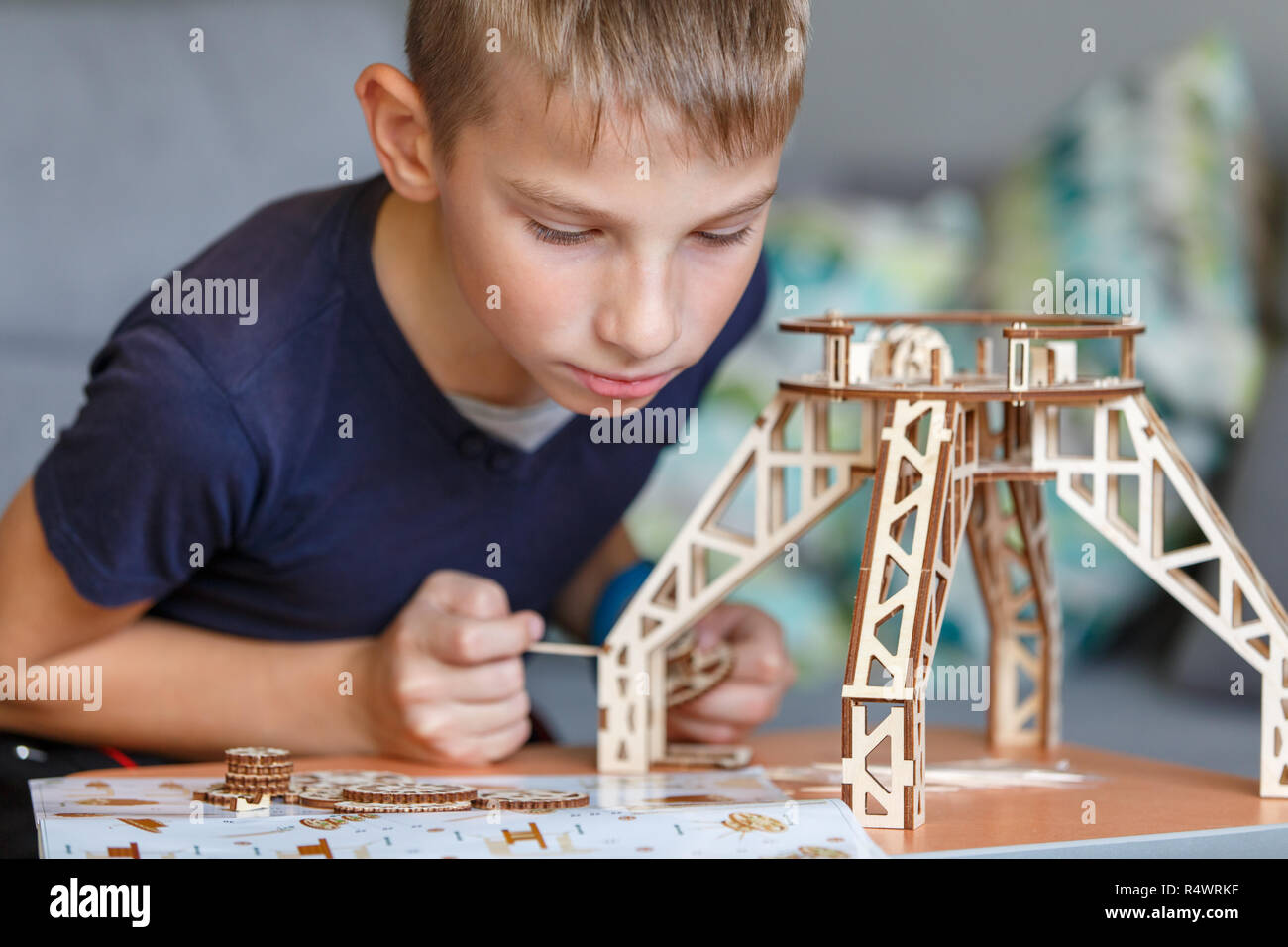 Young boy playing with wooden constructor. Eco building toy set background - Stock Image
