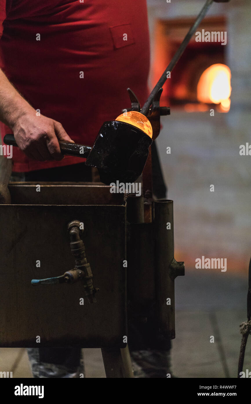 glass blower carefully forming hot glass to a decorative vase, germany - Stock Image