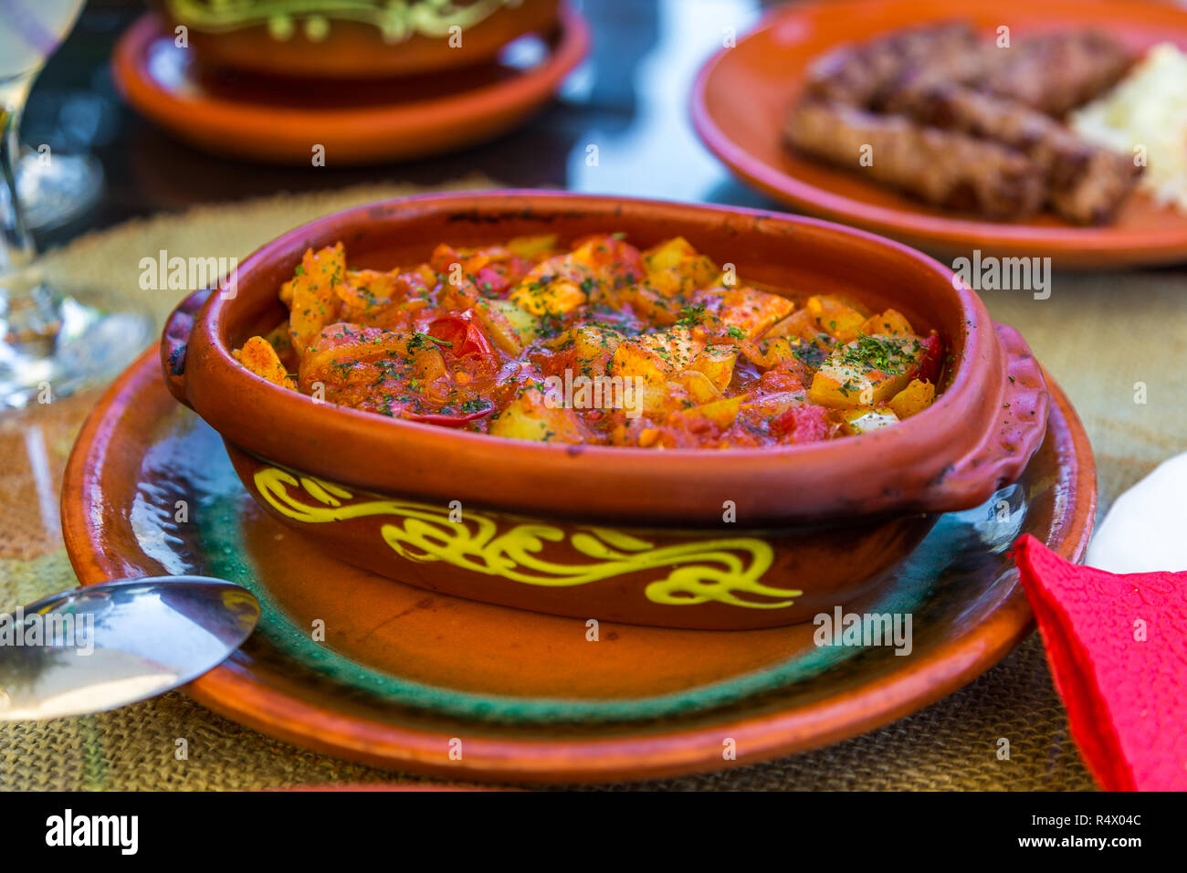 Balkan vegetable stew served in a traditional food clay dish. Zlatibor, Serbia. - Stock Image