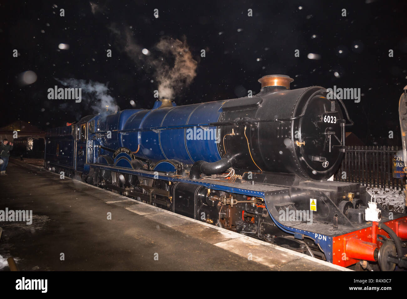 UK steam locomotive King Edward II alongside platform at Kidderminster's SVR station, in the dark, as snow flakes fall in the air -  like Christmas! - Stock Image
