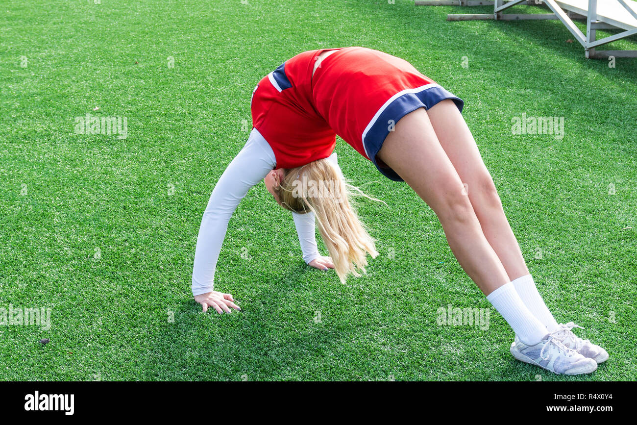 A high school cheerleader warming up on a green turf field in a back bend bridge position before she does a walk over. - Stock Image