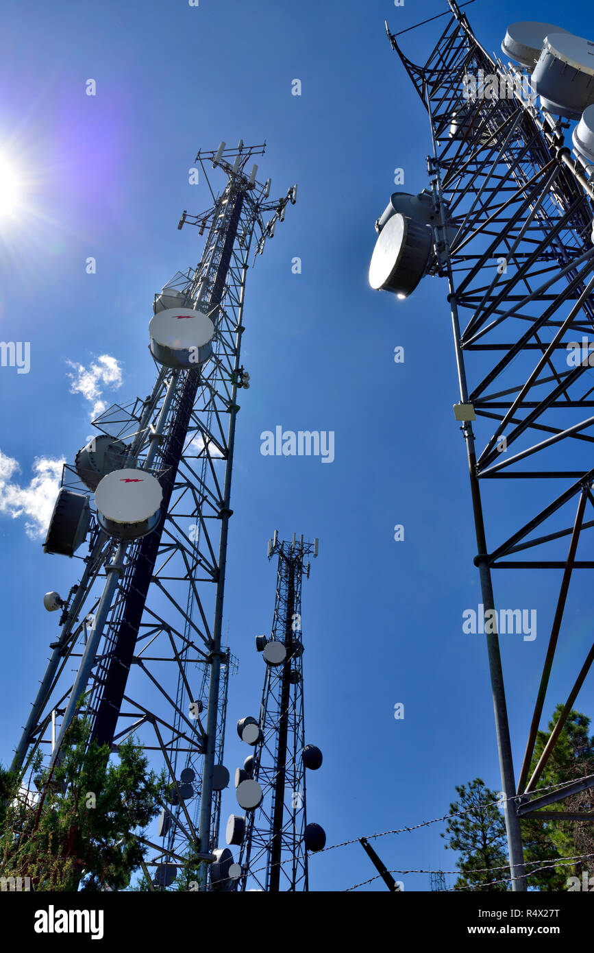 Communication towers with microwave and cell phone aerials Stock Photo