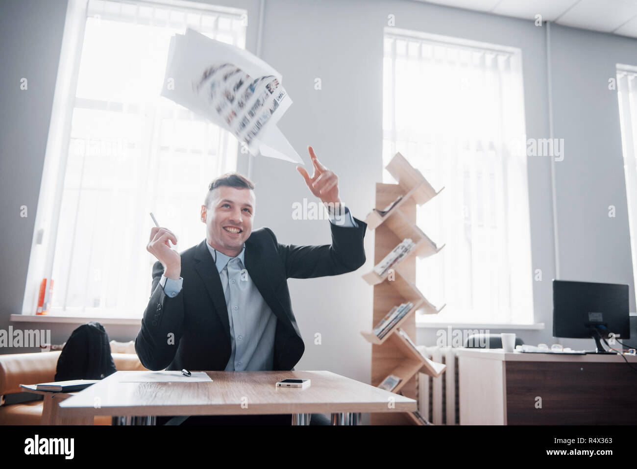 A handsome man sitting in the office and throwing papers on the air Stock Photo