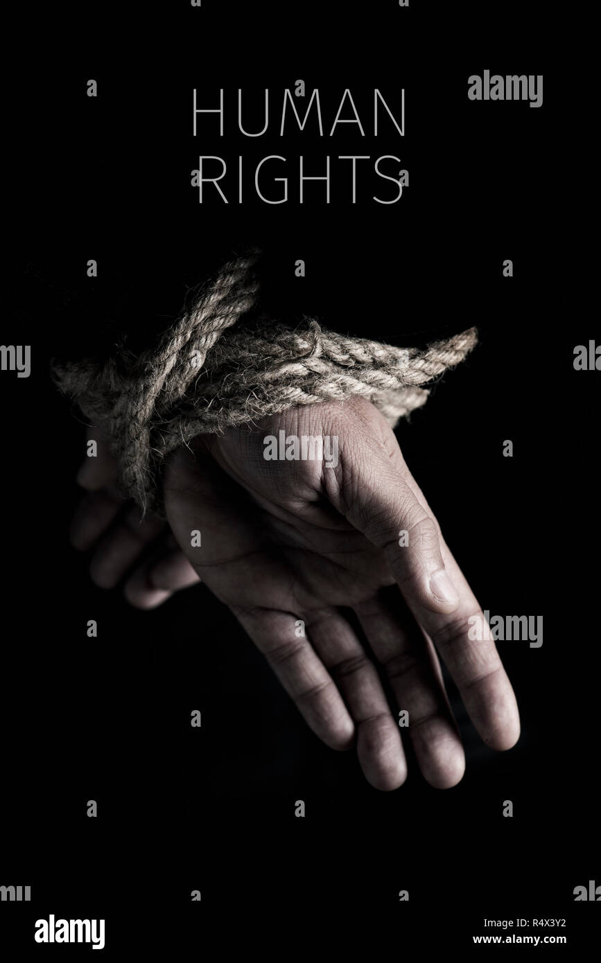 closeup of a man with his hands tied behind his back with rope, and the text human rights against a black background - Stock Image
