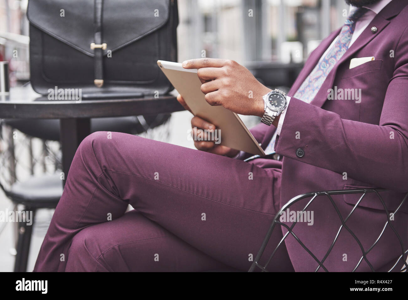 A beautiful African American businessman reads a menu in a cafe Stock Photo