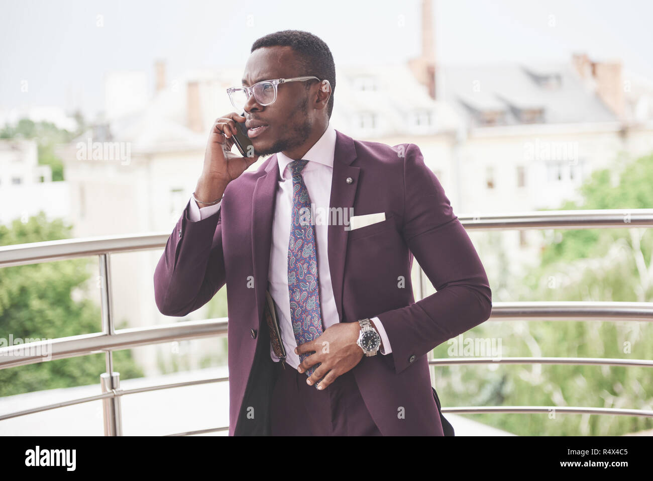 Portrait of a young and handsome African American businessman talking in a suit over the phone Stock Photo