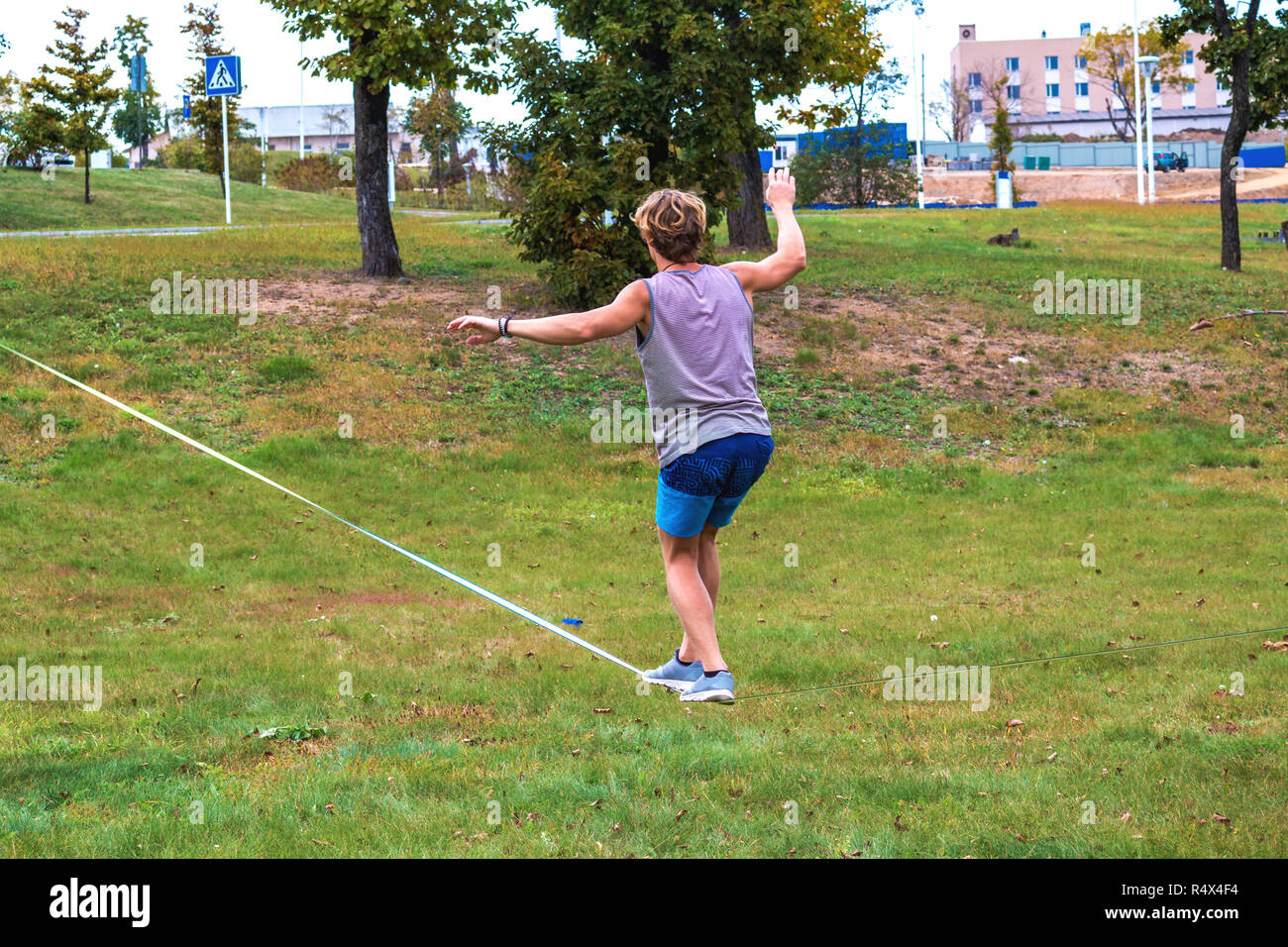 A young man in a public park learning to walk a tightrope. Slacklining is a practice in balance that typically uses nylon or polyester webbing tension Stock Photo