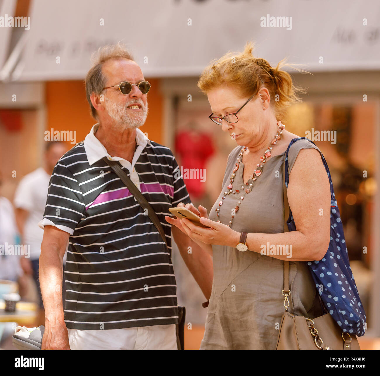 Tourist couple searching their way on mobile phone - Stock Image