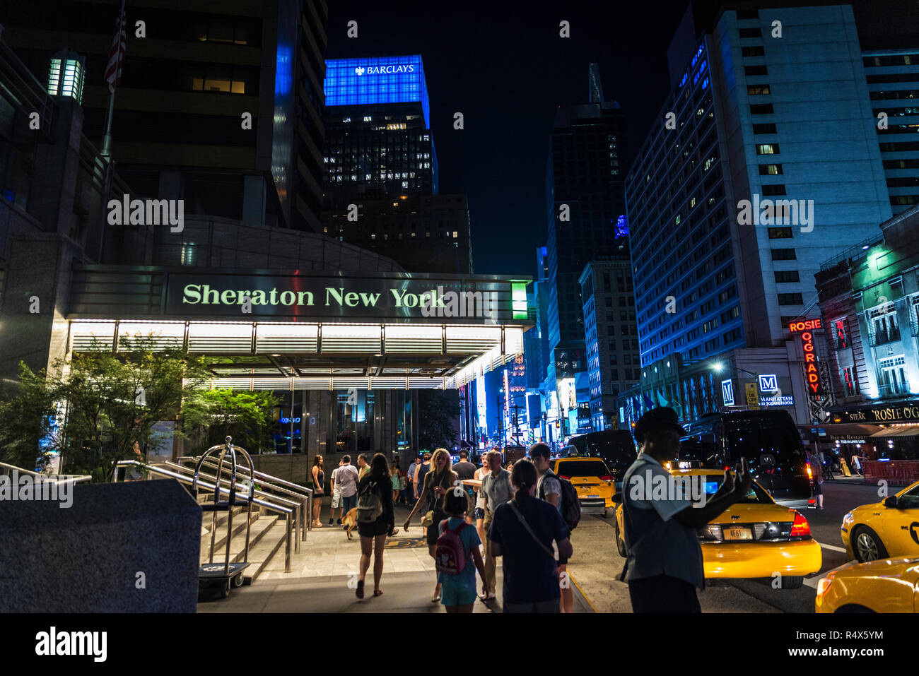 New York City, USA - July 30, 2018: Sheraton New York Times Square Hotel at night on Seventh Avenue (7th Avenue) next to Times Square with people arou - Stock Image