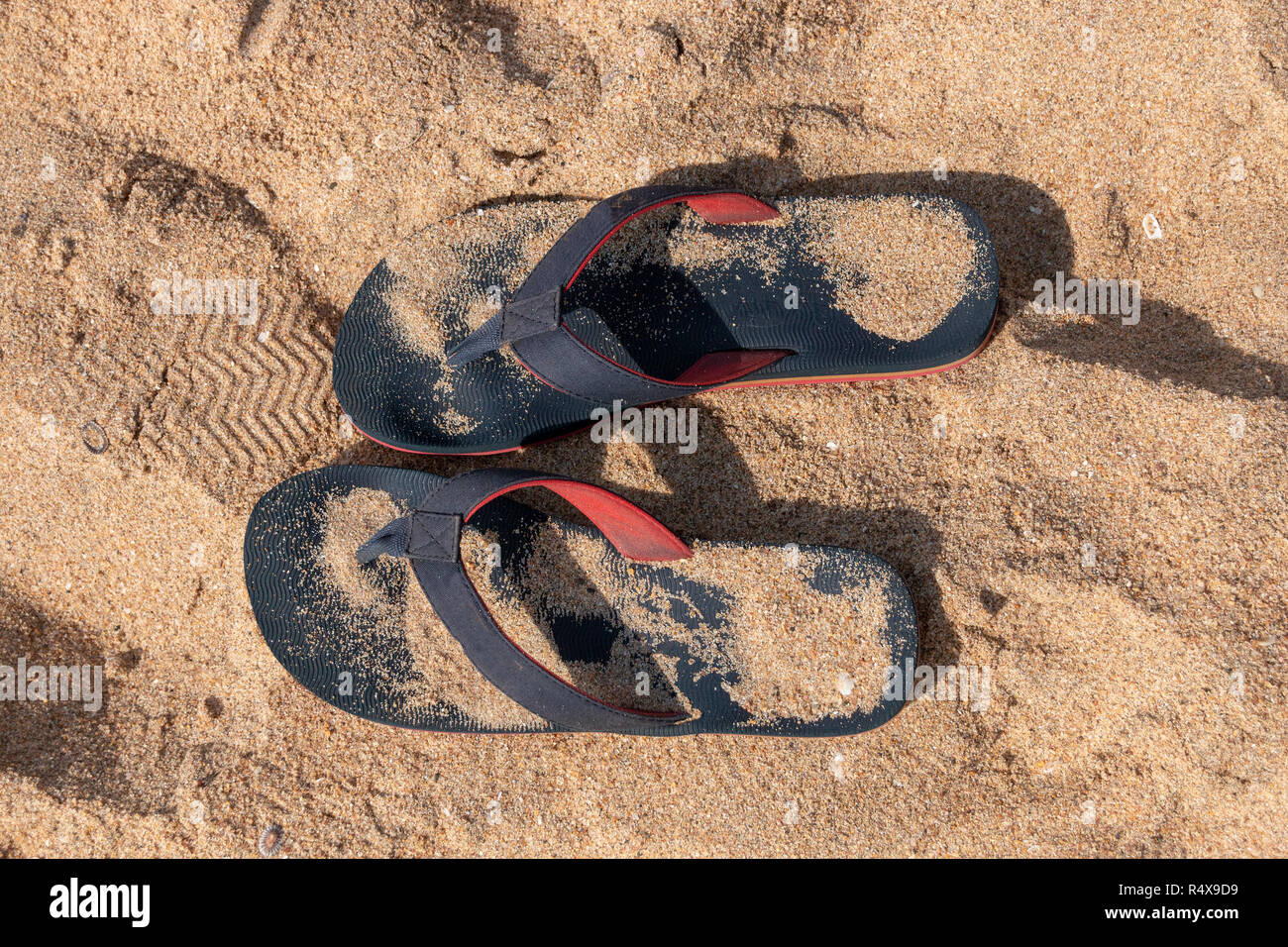 A Close up view of a pair of blue and red slops in the beach sand on a sunny summers day Stock Photo