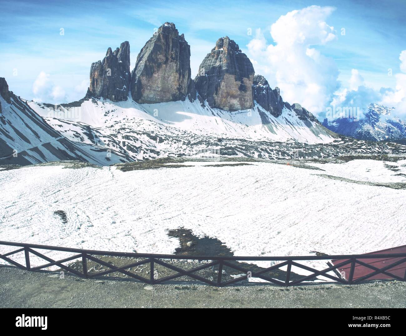 Magnificent view from terrace to symbol of Dolomite Alps - Tre Cime.  View from mountain hut with high rocky ridge in clouds on background. - Stock Image