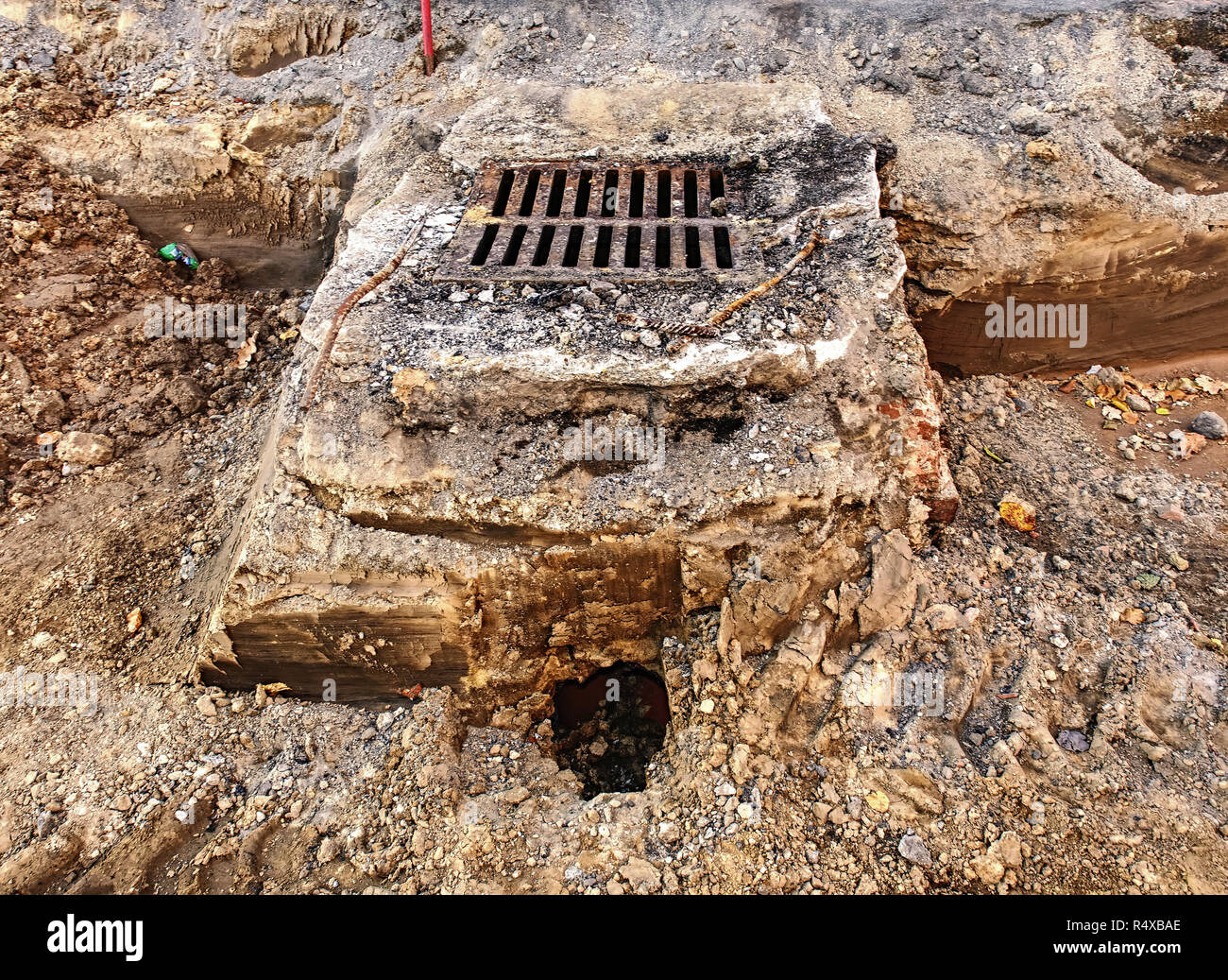 Sewer hole with cover in middle of square under reconstruction.  Semi cross section of sewer or drain grate under road. - Stock Image